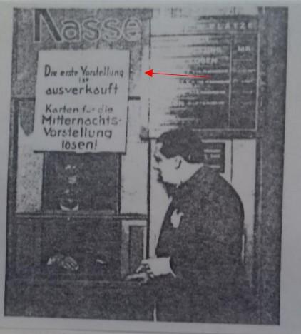 """Foto de noite de estreia. Vê-se Kurt Robitschek. Ao fundo destacada pela seta vermelha está uma placa com os seguintes dizeres: """"A primeira sessão está lotada. Compre aqui bilhetes para a sessão da meia noite."""""""