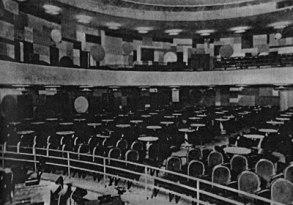 Interior do Teatro 950 lugares. Pode-se ver a distribuição de poltronas à frente do palco e na galeria, e mesas ao fundo.