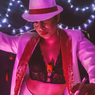 Juliana Farias, também conhecida como Divina Malandra, é atriz, performer, cabareta, dançarina, professora e coreógrafa. Integra a equipe do Cabaré Incoerente desde 2017, onde já atuou nos espetáculos Cabaré Carioca (2017 ); Cabaré Sade (2019), onde também assinou a coreografia na temporada de 2020 no Itaú Cultural; e no espetáculo virtual Noite Incoerente de Cabaré ( 2020). É bolsista do projeto, onde também atua como produtora das Noites Incoerentes de Cabaré. Com sua persona, Divina Malandra, pesquisa o erótico como burla e crítica social em seus números: O túnel Rebouças (2019) e A noite em que o vizinho tocou minha campainha (2020). Integra também mais dois coletivos de cabaré: o Beco da Serpente e o Coletivo Feminista Sussuaranas.